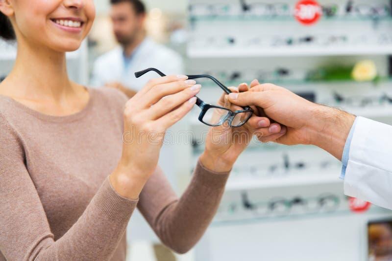 Κλείστε επάνω της γυναίκας με τα γυαλιά στο κατάστημα οπτικής στοκ εικόνα