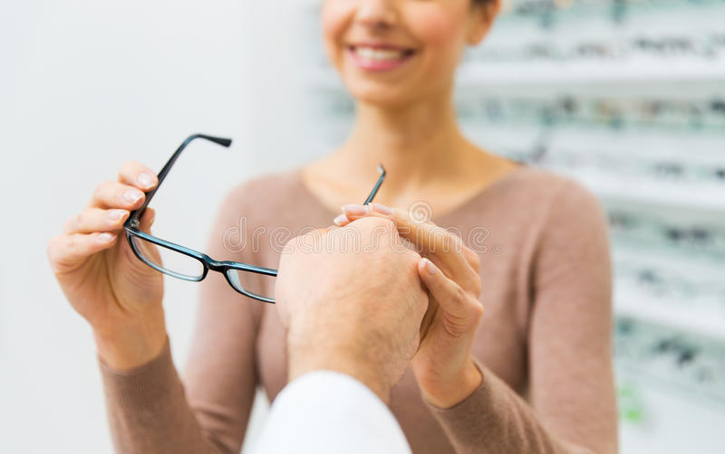 Κλείστε επάνω της γυναίκας με τα γυαλιά στο κατάστημα οπτικής στοκ φωτογραφίες