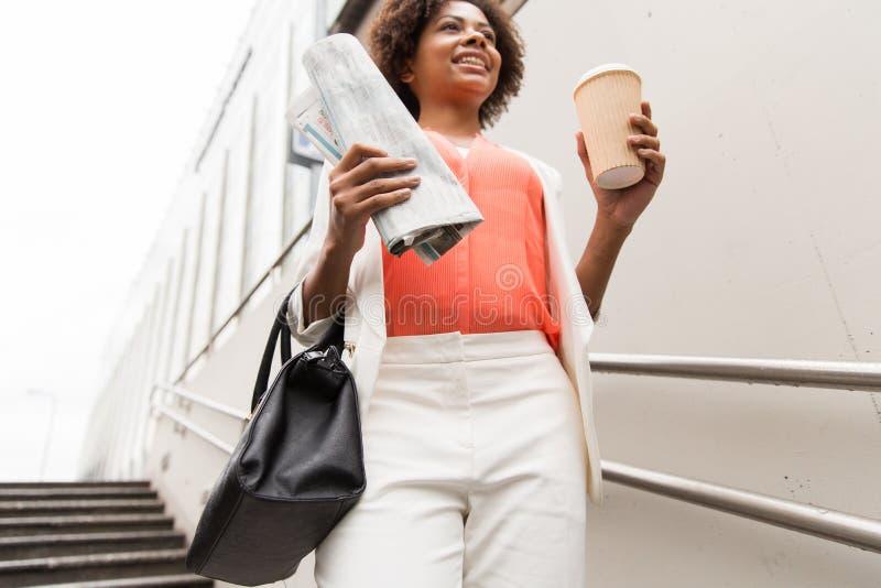 Κλείστε επάνω της γυναίκας με τον καφέ και την εφημερίδα στοκ εικόνα