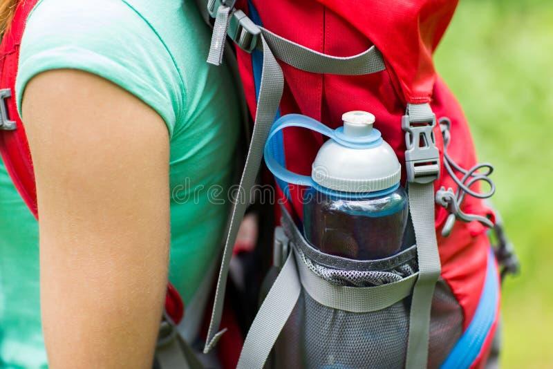 Κλείστε επάνω της γυναίκας με το μπουκάλι νερό στο σακίδιο πλάτης στοκ φωτογραφία με δικαίωμα ελεύθερης χρήσης