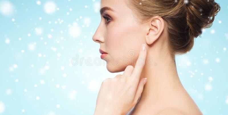 Κλείστε επάνω της γυναίκας που δείχνει το δάχτυλο το αυτί πέρα από το χιόνι στοκ φωτογραφία