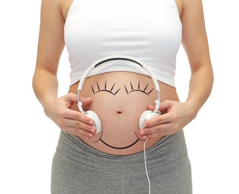 Κλείστε επάνω της εγκύου γυναίκας και των ακουστικών σε tummy στοκ εικόνα