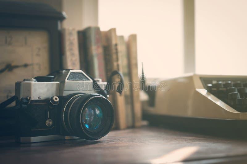 Κλείστε επάνω της εκλεκτής ποιότητας παλαιάς κάμερας, ρολόι, βιβλία, γραφομηχανή με το SU στοκ εικόνα με δικαίωμα ελεύθερης χρήσης
