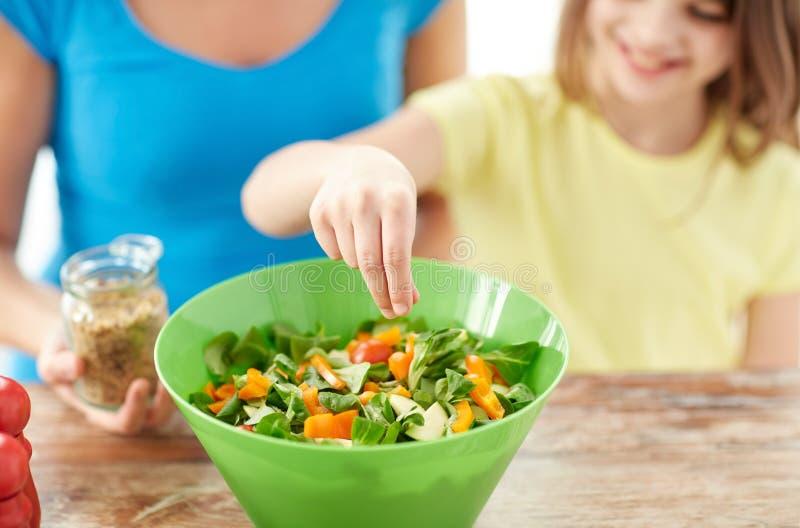 Κλείστε επάνω της ευτυχούς οικογενειακής μαγειρεύοντας σαλάτας στην κουζίνα στοκ εικόνες