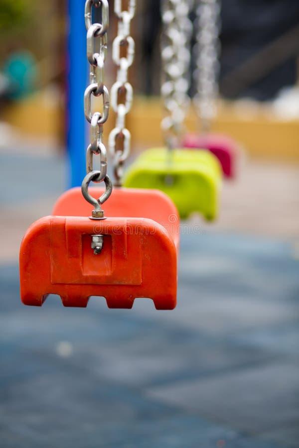 Κλείστε επάνω της κενής ταλάντευσης σε μια περιοχή παιχνιδιού παιδιών στο πάρκο στοκ εικόνα