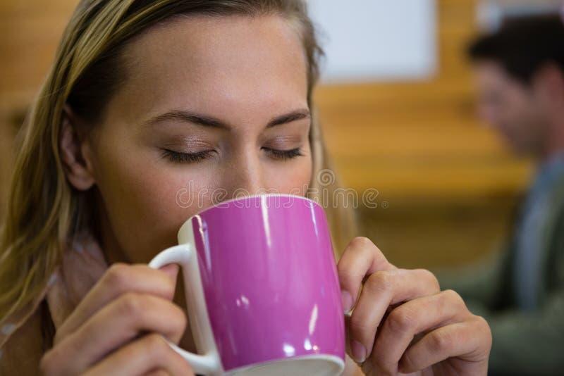 Κλείστε επάνω της νέας γυναίκας με τις προσοχές ιδιαίτερες κατοχή του καφέ στον καφέ στοκ εικόνα