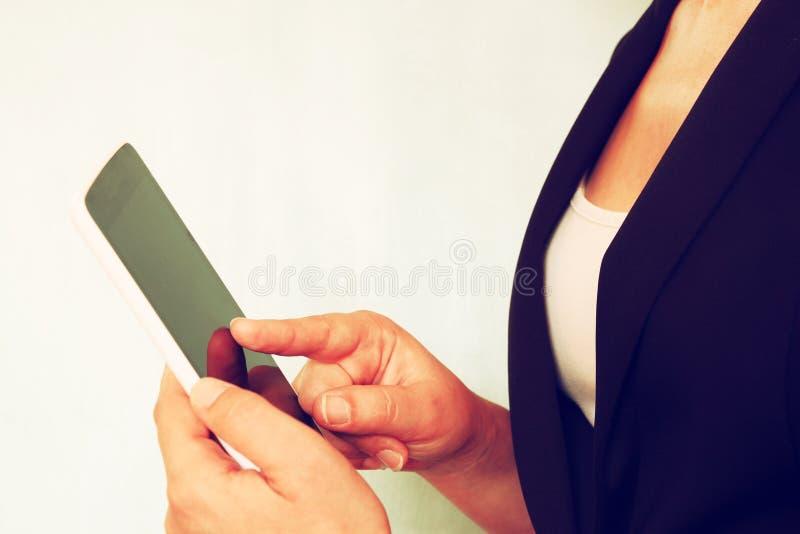 Κλείστε επάνω της νέας γυναίκας χρησιμοποιώντας τη συσκευή ταμπλετών λεπτό αναδρομικό φίλτρο στοκ εικόνες