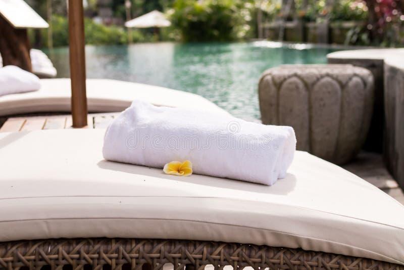 Κλείστε επάνω της πετσέτας με το frangipani plumeria στην καρέκλα γεφυρών στη λίμνη θερέτρου του Μπαλί όμορφη Ινδονησία νησιών ku στοκ φωτογραφία με δικαίωμα ελεύθερης χρήσης