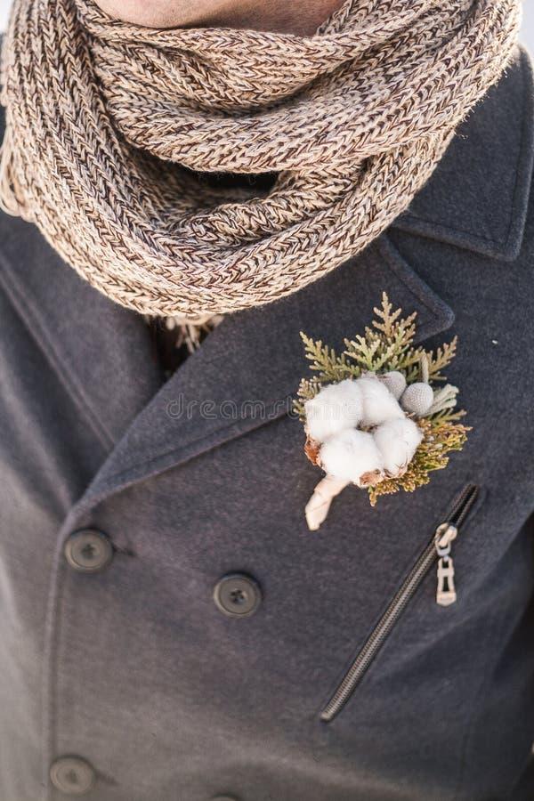 Κλείστε επάνω της όμορφης μπουτονιέρας με το λουλούδι βαμβακιού στο παλτό στοκ εικόνες
