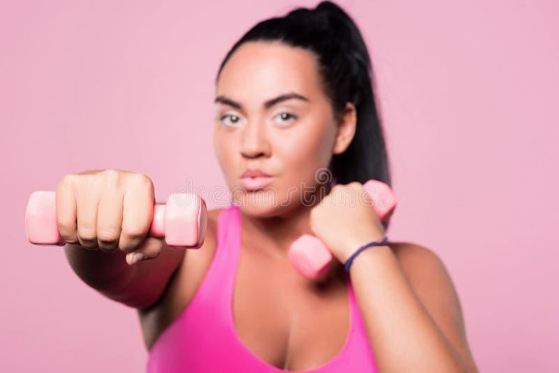 Κλείστε επάνω της chubby γυναίκας που κάνει τις ασκήσεις εγκιβωτισμού με τους αλτήρες στοκ εικόνα με δικαίωμα ελεύθερης χρήσης