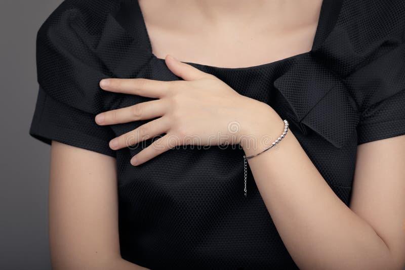 Κλείστε επάνω τη λεπτομέρεια ενός βραχιολιού σε ένα θηλυκό πρότυπο χεριών στοκ φωτογραφία