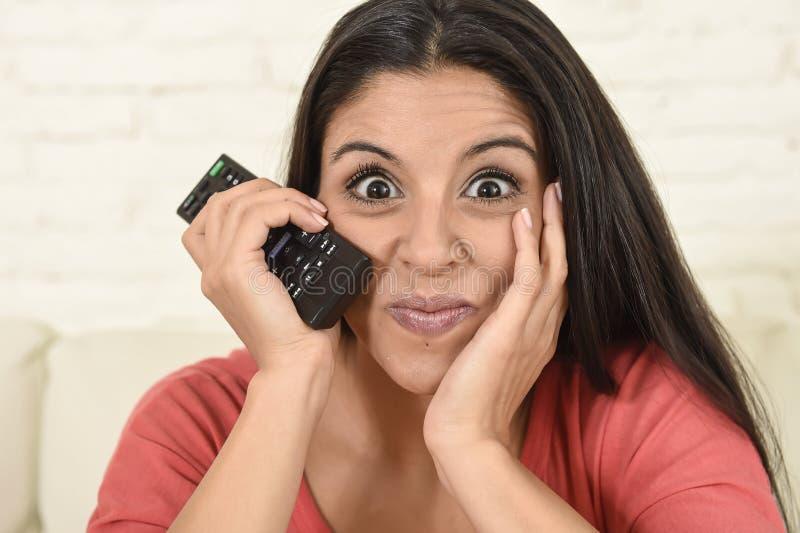 Κλείστε επάνω τη νέα όμορφη ισπανική τηλεόραση εγχώριας προσοχής γυναικών πορτρέτου σε ευτυχή καναπέδων συγκινημένη στοκ εικόνα