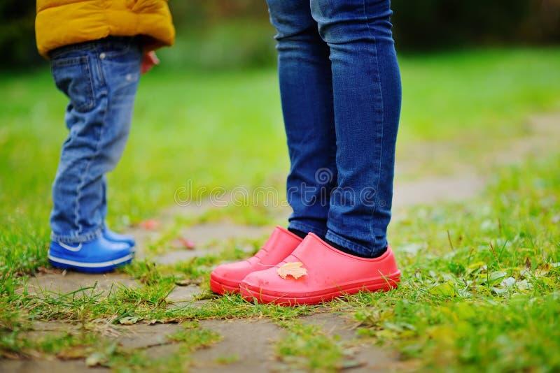 Κλείστε επάνω τη φωτογραφία του παιδιού και των ενήλικων ποδιών στις λαστιχένιες μπότες στοκ φωτογραφίες