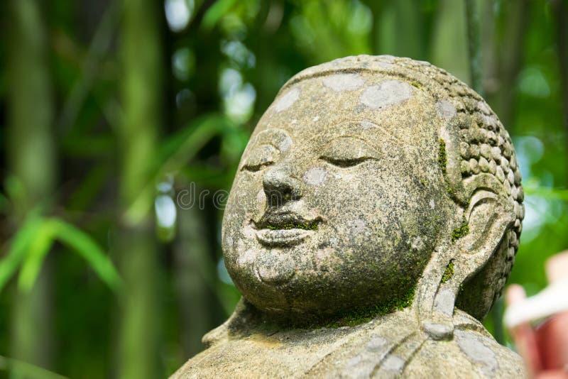 Κλείστε επάνω τον επικεφαλής Βούδα χάρασε από την πέτρα στο πάρκο μπαμπού στοκ φωτογραφία