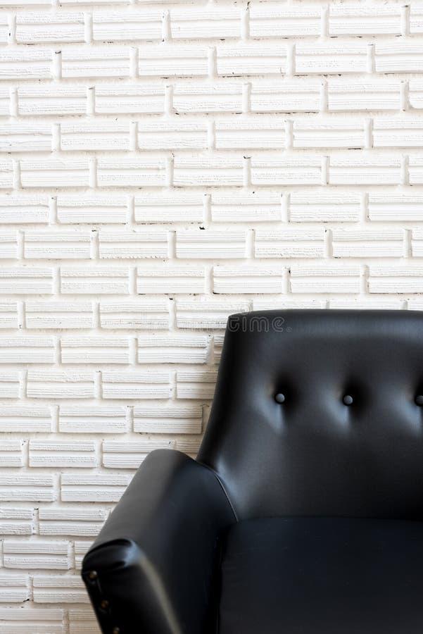 Κλείστε επάνω τον κλασικό μαύρο καναπέ και τον άσπρο τουβλότοιχο στοκ φωτογραφίες με δικαίωμα ελεύθερης χρήσης