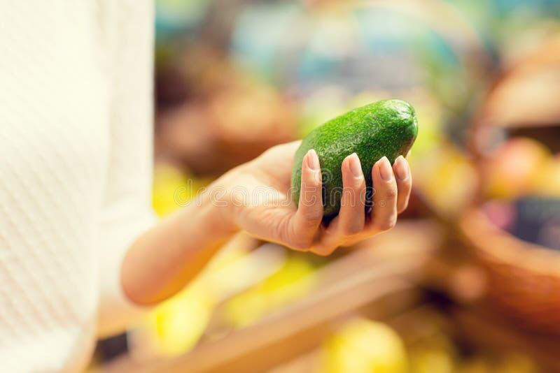 Κλείστε επάνω του αβοκάντο εκμετάλλευσης χεριών γυναικών στην αγορά στοκ εικόνα