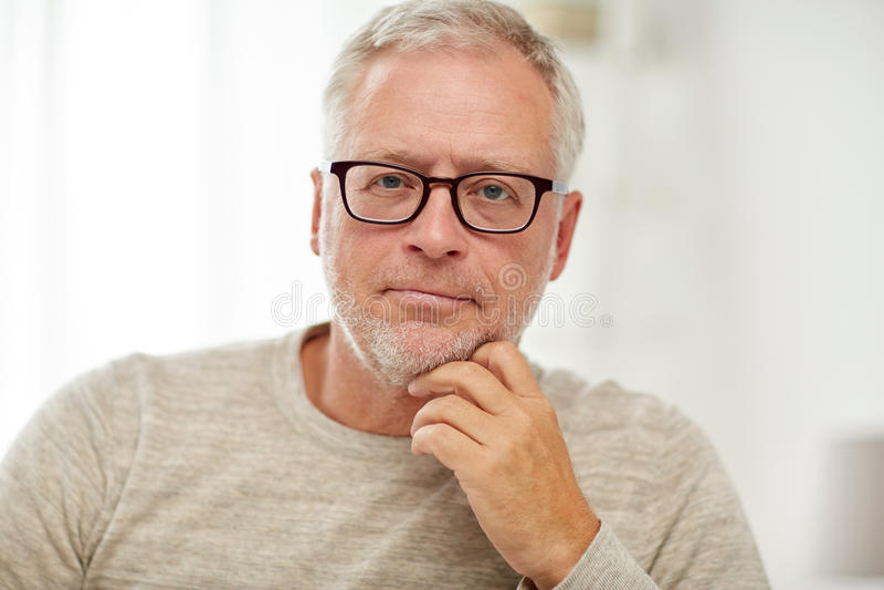 Κλείστε επάνω του ανώτερου ατόμου στη σκέψη γυαλιών στοκ εικόνα
