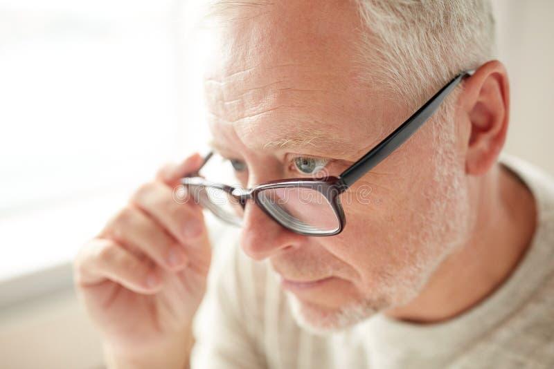 Κλείστε επάνω του ανώτερου ατόμου στο κοίταγμα γυαλιών στοκ φωτογραφία