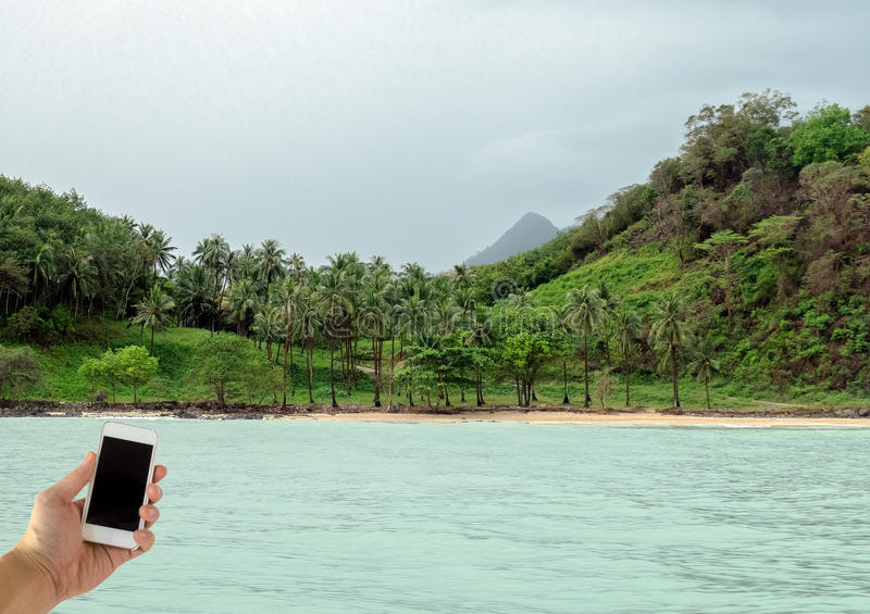 Κλείστε επάνω του αρσενικού έξυπνου κινητού τηλεφώνου εκμετάλλευσης χεριών με την κενή οθόνη στην μπλε θάλασσα με Copyspace που χ στοκ εικόνες