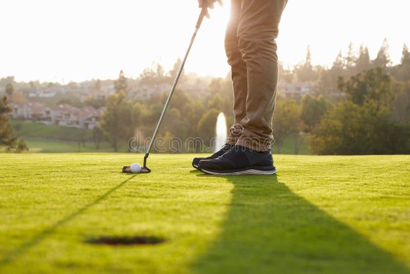 Κλείστε επάνω του αρσενικού παίκτη γκολφ που παρατάσσει Putt σε πράσινο στοκ φωτογραφία με δικαίωμα ελεύθερης χρήσης
