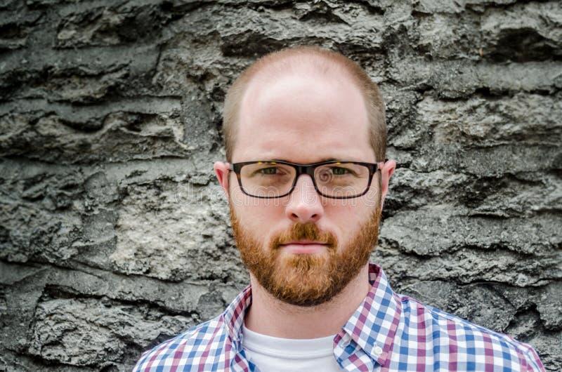 Κλείστε επάνω του ατόμου με τα γυαλιά ενάντια στον πέτρινο τοίχο στοκ φωτογραφία με δικαίωμα ελεύθερης χρήσης