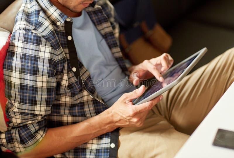 Κλείστε επάνω του ατόμου με τη συνεδρίαση PC ταμπλετών στον καφέ στοκ φωτογραφία