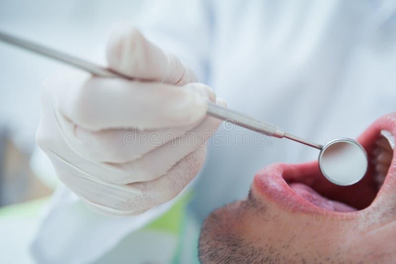 Κλείστε επάνω του ατόμου που έχει τα δόντια του εξετασμένων στοκ φωτογραφία