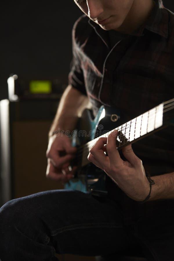 Κλείστε επάνω του ατόμου που παίζει την ηλεκτρική κιθάρα στο στούντιο στοκ φωτογραφία