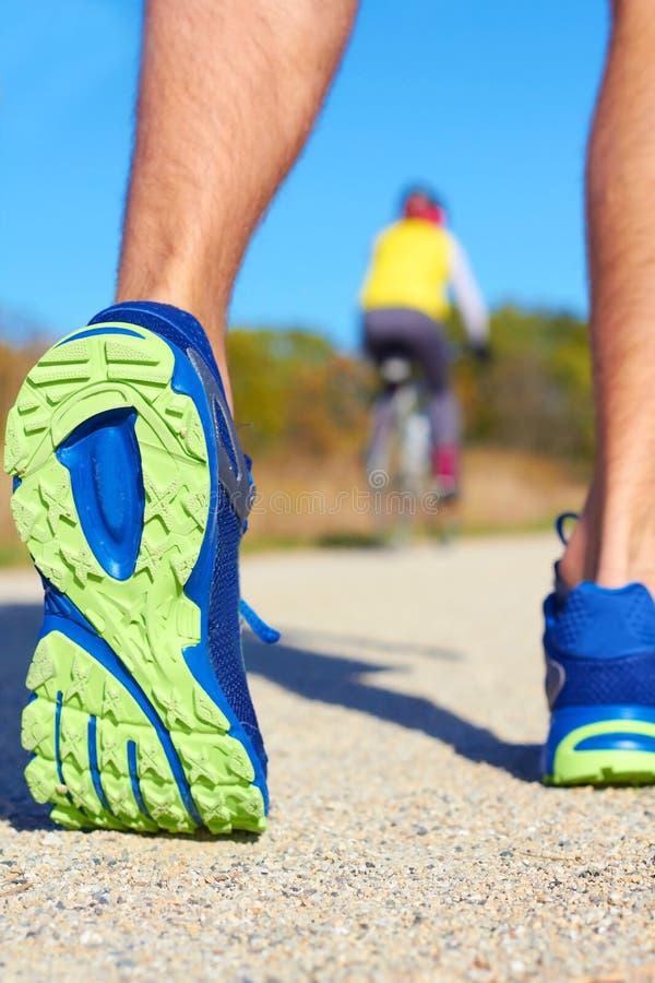 Κλείστε επάνω του ατόμου που περπατά στη φύση με τον ποδηλάτη στο υπόβαθρο στοκ εικόνα με δικαίωμα ελεύθερης χρήσης