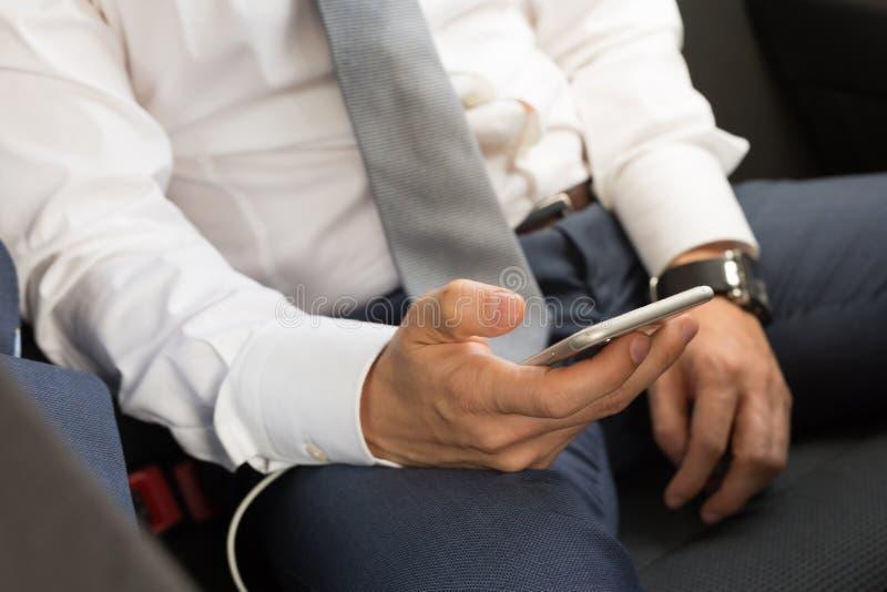 Κλείστε επάνω του επιχειρηματία χρησιμοποιώντας το κινητό έξυπνο τηλέφωνο σε ένα αυτοκίνητο στοκ εικόνες