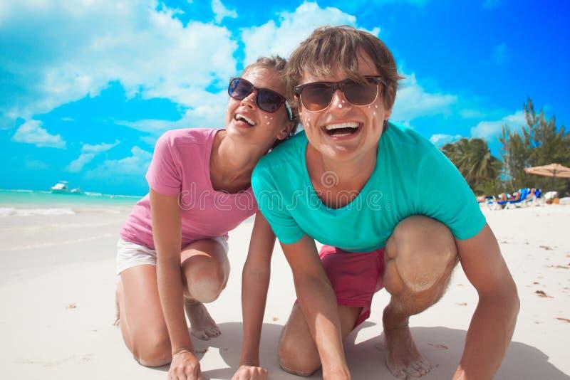 Κλείστε επάνω του ευτυχούς νέου καυκάσιου ζεύγους στα γυαλιά ηλίου που χαμογελά στην παραλία στοκ εικόνα