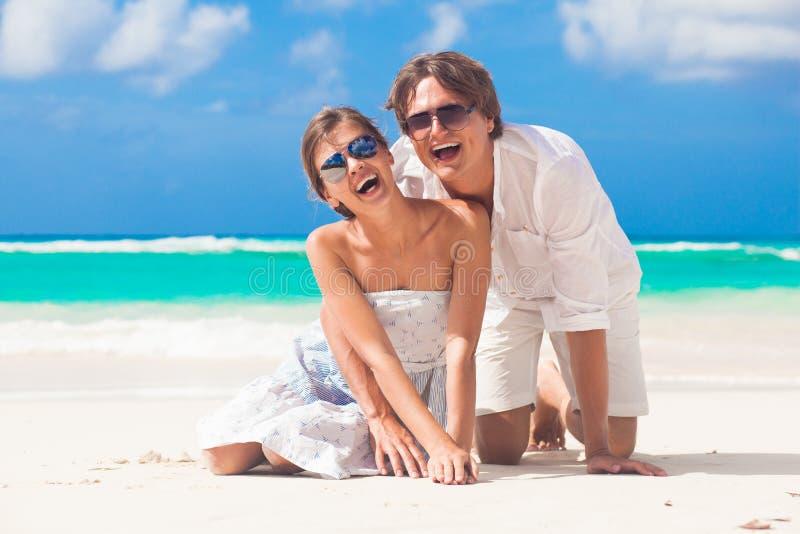 Κλείστε επάνω του ευτυχούς νέου καυκάσιου ζεύγους στα γυαλιά ηλίου που χαμογελά στην παραλία στοκ φωτογραφία