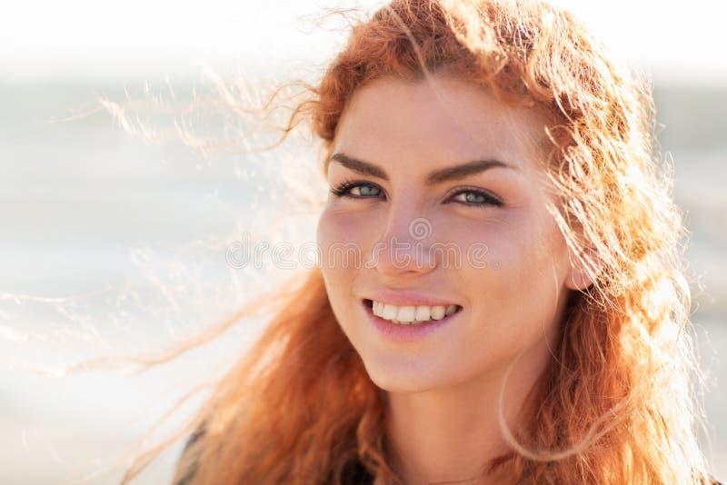 Κλείστε επάνω του ευτυχούς νέου redhead προσώπου γυναικών στοκ φωτογραφία