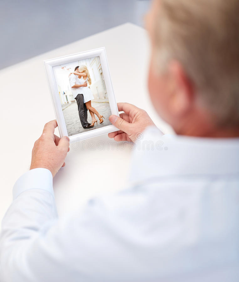 Κλείστε επάνω του ηληκιωμένου που κρατά τη νέα φωτογραφία ζευγών στοκ εικόνα με δικαίωμα ελεύθερης χρήσης