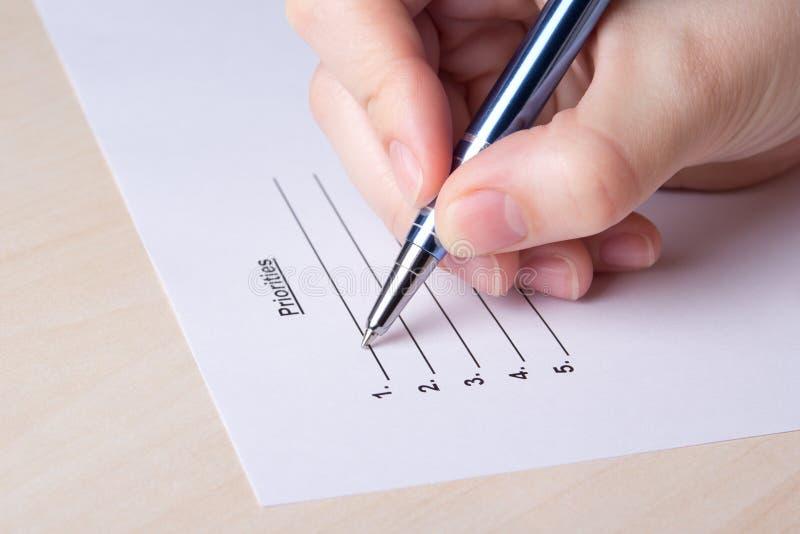 Κλείστε επάνω του θηλυκού καταλόγου προτεραιοτήτων πλήρωσης χεριών με τη μάνδρα στοκ εικόνες