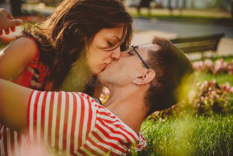 Κλείστε επάνω του καλού ζεύγους στην πράσινη χλόη στο πάρκο, το χρόνο φιλήματος και εξόδων από κοινού στοκ εικόνες