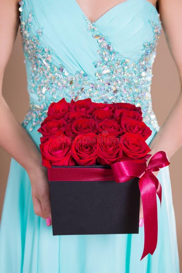 Κλείστε επάνω του κιβωτίου με τα κόκκινα ροδαλά λουλούδια στα θηλυκά χέρια στοκ φωτογραφία με δικαίωμα ελεύθερης χρήσης