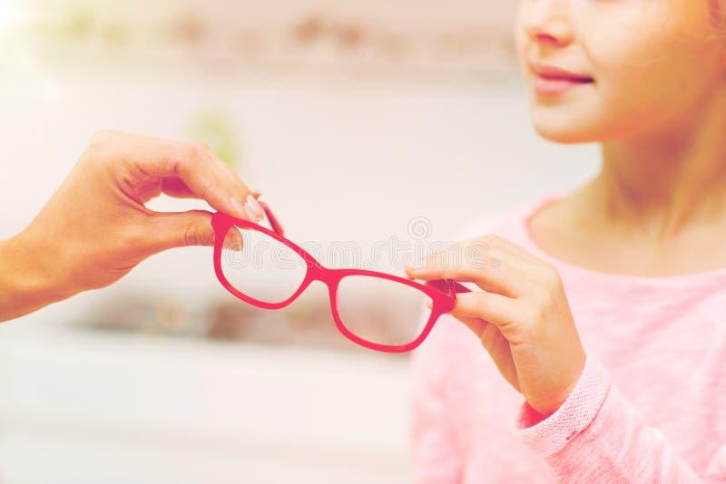 Κλείστε επάνω του κοριτσιού που παίρνει τα γυαλιά στο κατάστημα οπτικής στοκ εικόνα με δικαίωμα ελεύθερης χρήσης