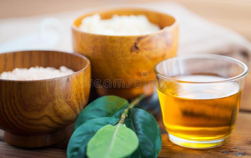Κλείστε επάνω του μελιού στο γυαλί με τα φύλλα στο ξύλο στοκ φωτογραφίες