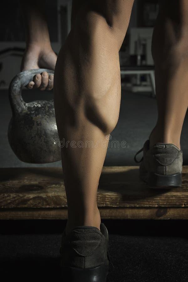 Κλείστε επάνω του μυϊκού ποδιού bodybuilders που κάνει τις ασκήσεις με τα βάρη στοκ εικόνες