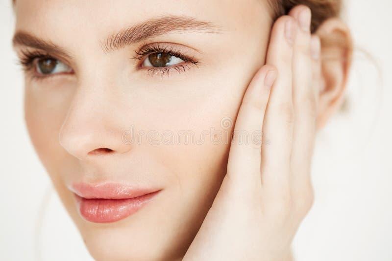 Κλείστε επάνω του νέου όμορφου χαμόγελου κοριτσιών σχετικά με το πρόσωπο πέρα από το άσπρο υπόβαθρο Υγεία ομορφιάς SPA και cosmet στοκ εικόνα με δικαίωμα ελεύθερης χρήσης