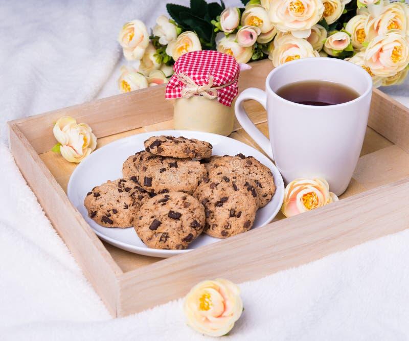 Κλείστε επάνω του ξύλινου δίσκου με τα μπισκότα τσιπ σοκολάτας, φλυτζάνι του τσαγιού, στοκ εικόνες