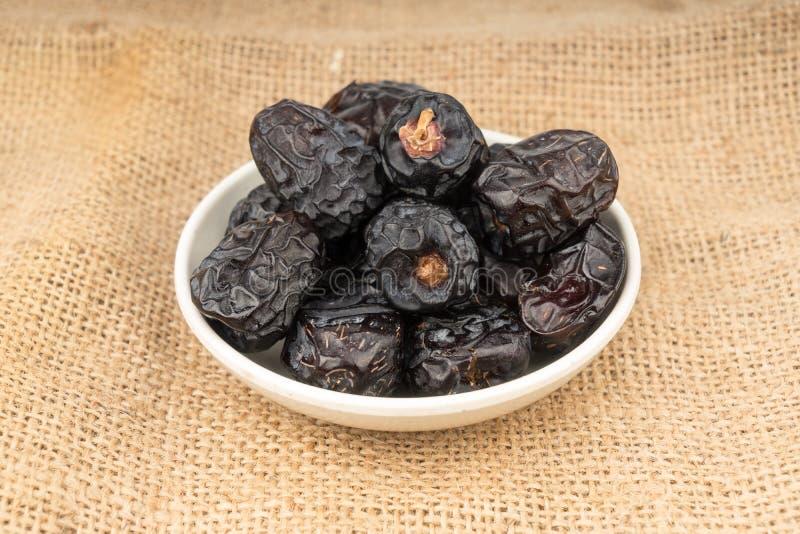 Κλείστε επάνω του ξύλινου κουταλιού με τα ξηρά φρούτα ημερομηνιών sackcloth στοκ φωτογραφία