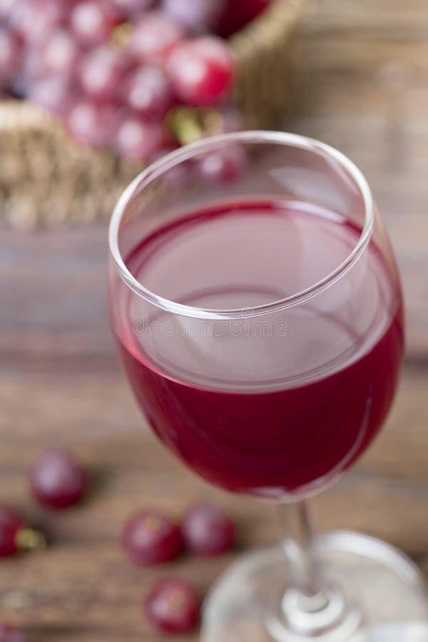 Κλείστε επάνω του ποτηριού του χυμού κρασιού ή σταφυλιών και των φρούτων στο ξύλινο TA στοκ εικόνες