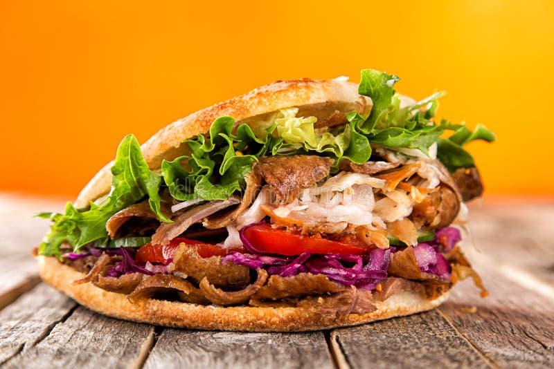 Κλείστε επάνω του σάντουιτς kebab στον παλαιό ξύλινο πίνακα στοκ εικόνες