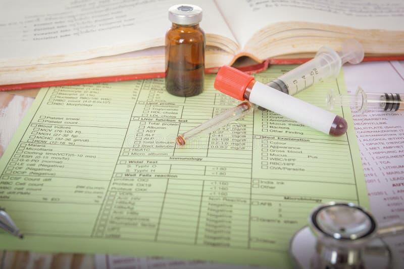 Κλείστε επάνω του στηθοσκοπίου στη μορφή στα αποτελέσματα των εξετάσεων αίματος βιοχημείας με το βιβλίο και το φιαλίδιο στοκ φωτογραφία με δικαίωμα ελεύθερης χρήσης