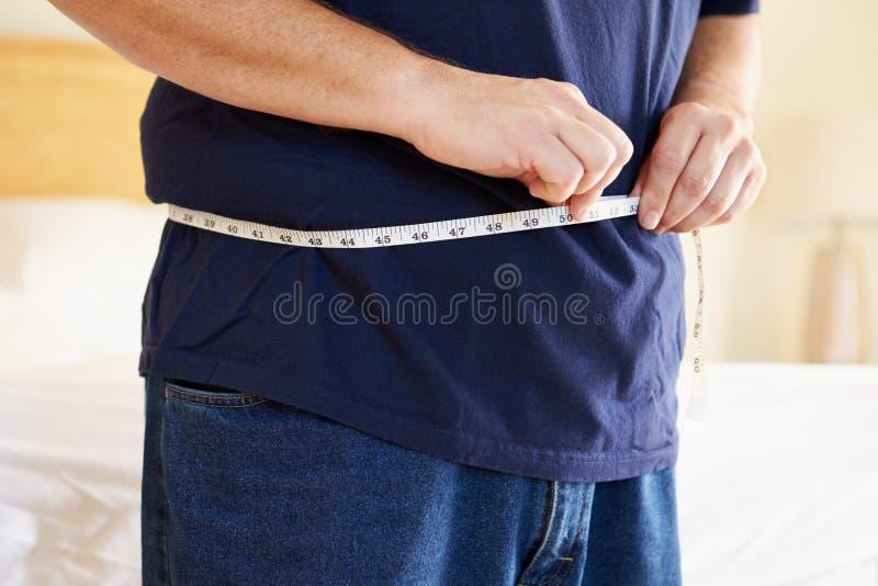 Κλείστε επάνω του υπέρβαρου ατόμου που μετρά τη μέση στοκ εικόνες