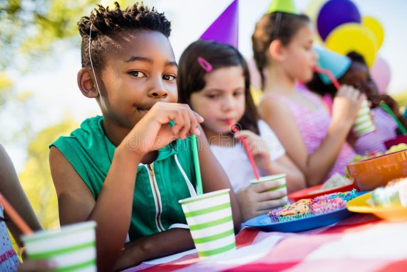 Κλείστε επάνω του χαριτωμένου αγοριού που πίνει κάτι κατά τη διάρκεια μιας γιορτής γενεθλίων στοκ εικόνα με δικαίωμα ελεύθερης χρήσης