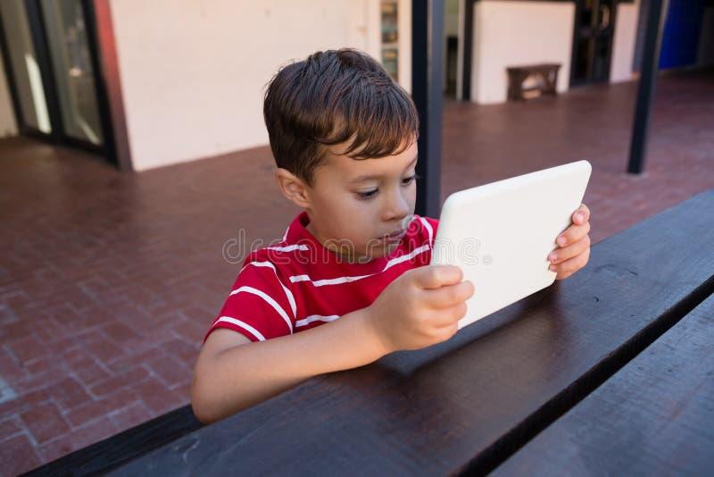 Κλείστε επάνω του χαριτωμένου αγοριού χρησιμοποιώντας το ψηφιακό lap-top καθμένος στον πίνακα στοκ φωτογραφίες με δικαίωμα ελεύθερης χρήσης