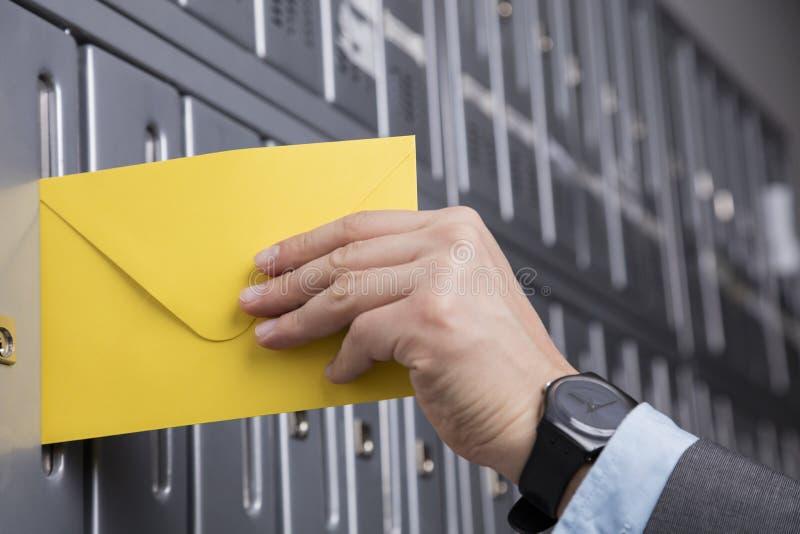 Κλείστε επάνω του χεριού βάζοντας την κίτρινη επιστολή στην ταχυδρομική θυρίδα στοκ εικόνες με δικαίωμα ελεύθερης χρήσης